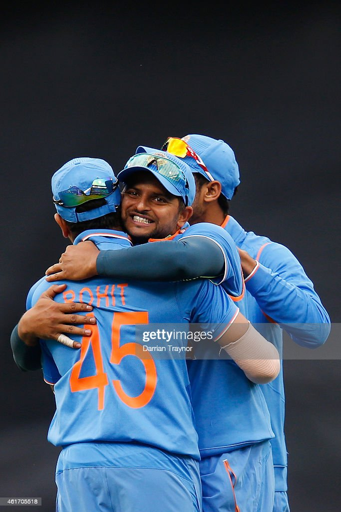 Suresh Raina of India embraces Rohit Sharma after taking a catch to dismiss David Warner of Australia during the One Day International match between Australia and India at Melbourne Cricket Ground on January 18, 2015 in Melbourne, Australia.