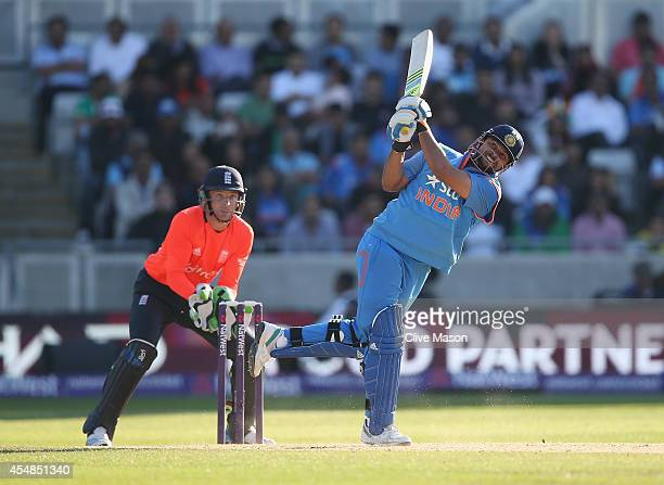 Suresh Raina of India hits out as Jos Buttler of England looks on during the NatWest International T20 2014 match between England and India at...