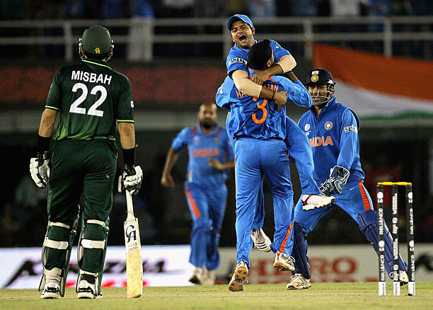 Suresh Raina of India leaps into the arms of team mate Harbhajan Singh with team mate MS Dhoni ad MisbahulHaq of Pakistan looking on after Singh...