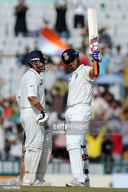 Suresh Raina of India raises his bat beside teammate Sachin Tendulkar after scoring a half century during day three of the First Test match between...