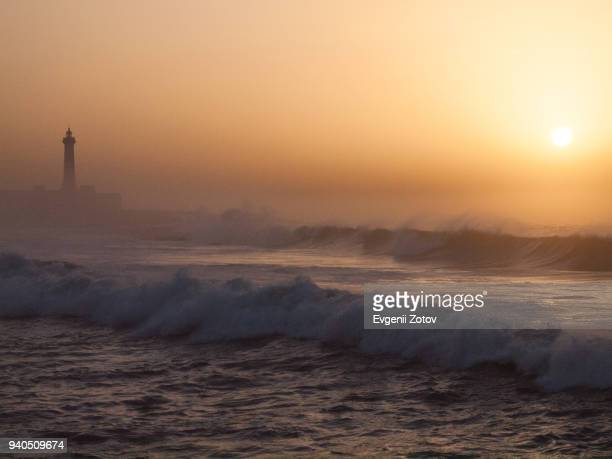 Surf and silhouette of lighthouse at sunset. Rabat, Morocco