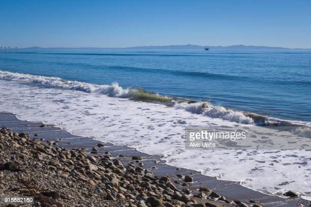 Surf breaks on Haskell's Beach in Santa Barbara, California with Channel Islands NP and oil rig distant.