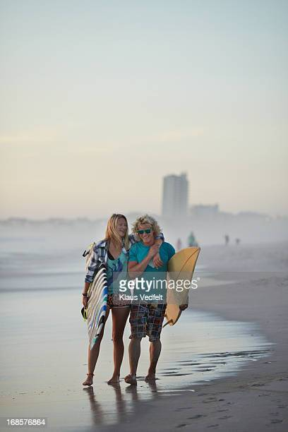 surf couple walking along the coast with boards - women in wet t shirts stock pictures, royalty-free photos & images
