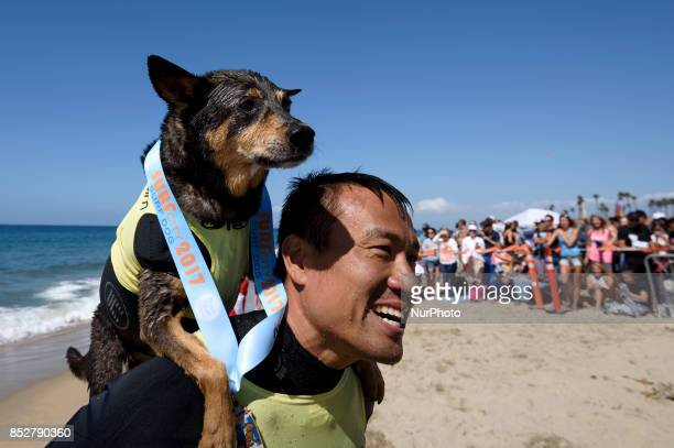 Surf dog Abbie an Australian Kelpie and owner Michael Uy after competing in the Surf City Surf Dog competition in Huntington Beach California on...