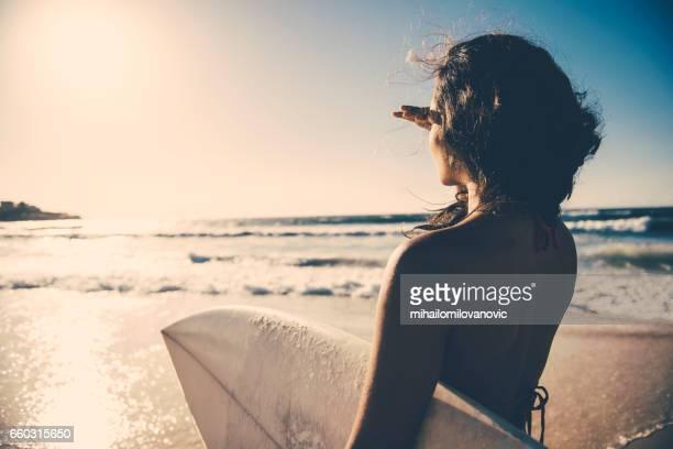 garota surf, olhando para a distância - surfe - fotografias e filmes do acervo