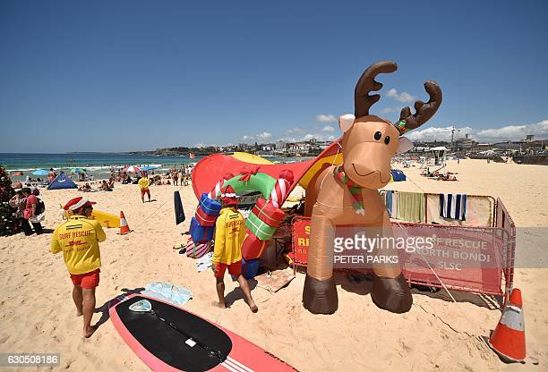 Surf lifesavers walk past a Christmas tree and an inflatable reindeer on Bondi Beach on Christmas Day in Sydney on December 25 2016 / AFP / PETER...