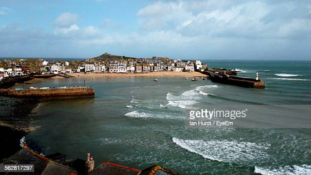 surf on beach with city in background - penzance stock pictures, royalty-free photos & images