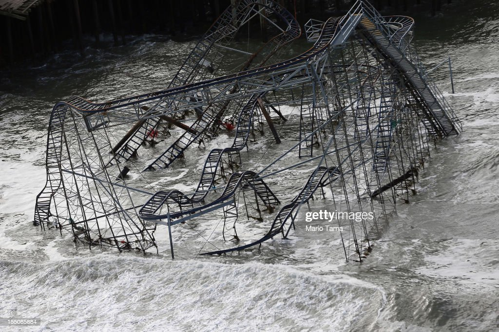 Surf rolls past a destroyed roller coaster wrecked by Superstorm Sandy on October 31, 2012 in Seaside Heights, New Jersey. At least 50 people were reportedly killed in the U.S. by Sandy with New Jersey suffering massive damage and power outages.