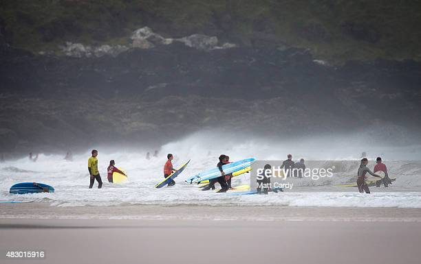 A surf school enters the water as a heat of the UK Pro Surf Association's Men's Open takes place nearby on Fistral Beach on the first day of the...