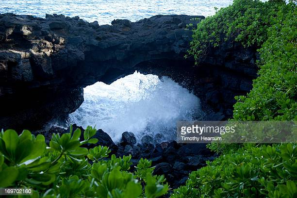 surf splashes through collapsed lava tube - timothy hearsum stock-fotos und bilder