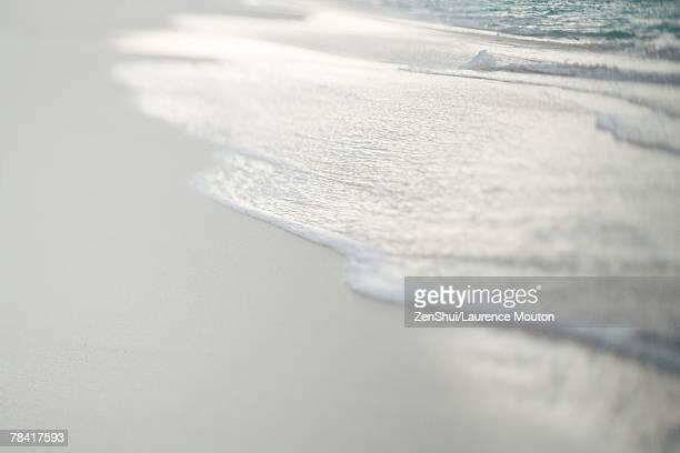 Surf washing up on sand, close-up