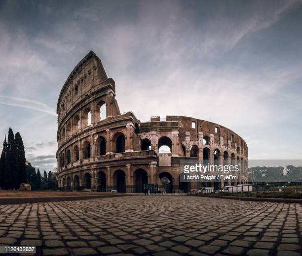 surface level image of coliseum against sky during sunset - colosseum stock pictures, royalty-free photos & images