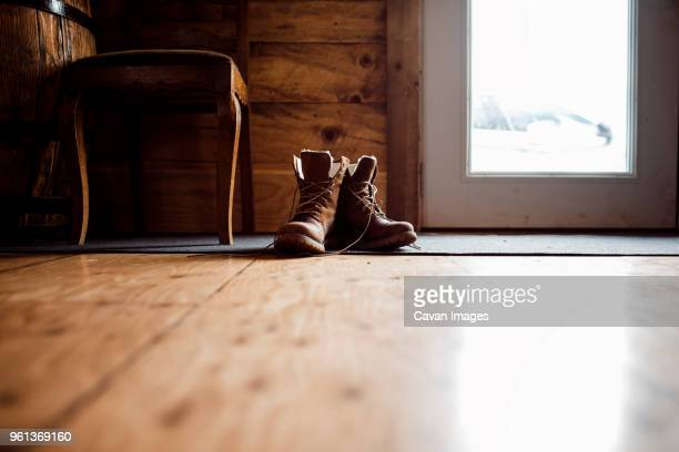 surface level image of leather boots on floor at home - leather boot stock pictures, royalty-free photos & images