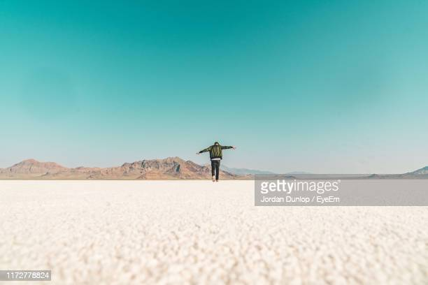 surface level image of man with arms outstretched walking on land against clear sky - salt flat stock pictures, royalty-free photos & images