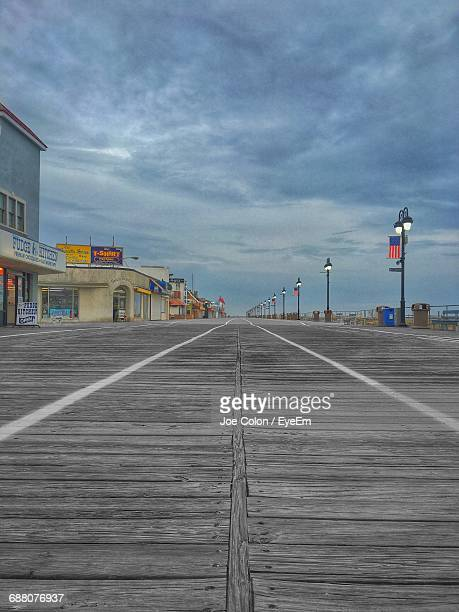 Surface Level Of Boardwalk Against Cloudy Sky During Sunset