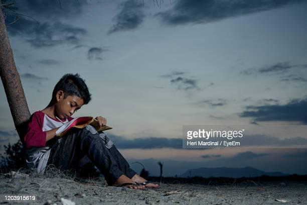 surface level of boy studying by tree at dusk - heri mardinal stock pictures, royalty-free photos & images