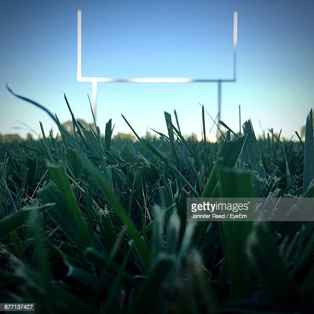 Surface Level Of Football Goal Post On Grassy Field Against Clear Sky