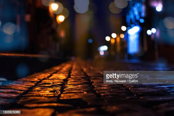 surface level of illuminated street at night - direction stock pictures, royalty-free photos & images