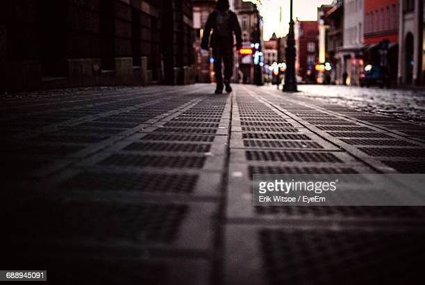Surface Level Of Man Walking On Illuminated Street During Sunset