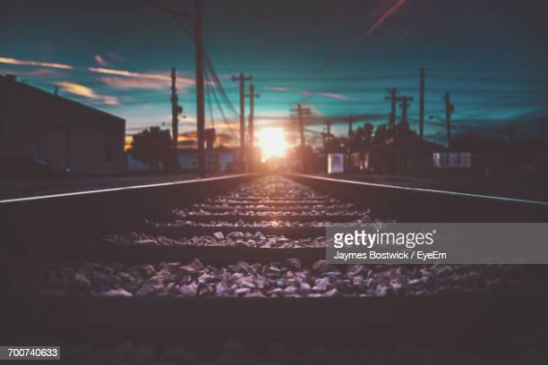 Surface Level Of Railroad Tracks Against Sky During Sunset