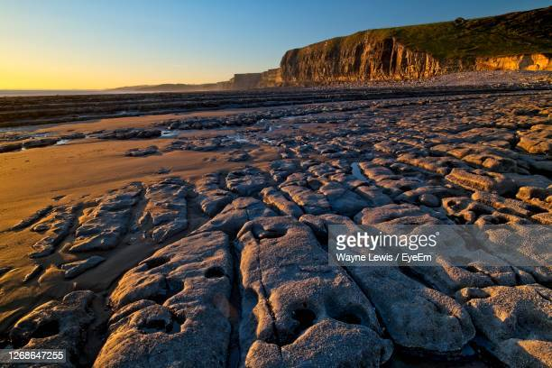 surface level of rocky beach and  land against cliffs and sky during sunset - geology stock pictures, royalty-free photos & images