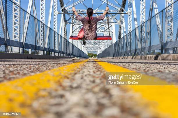 surface level of woman swinging on bridge - florin seitan stock pictures, royalty-free photos & images