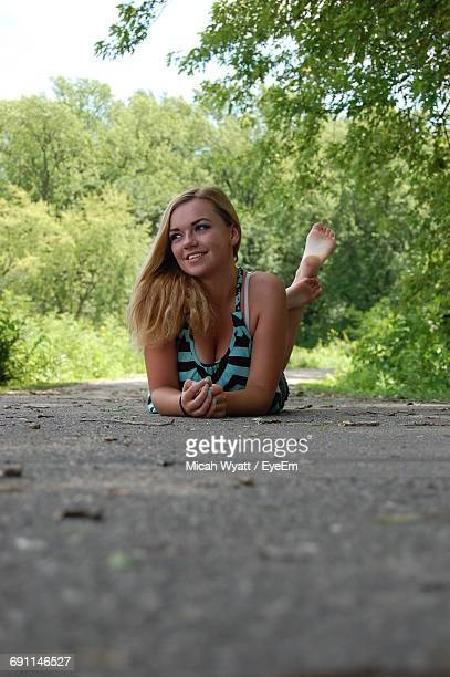 Surface Level Of Young Woman Lying On Road In Forest