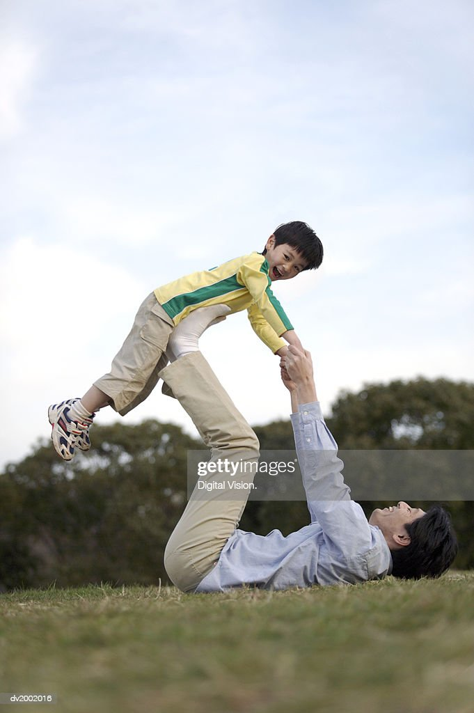 Surface Level Shot of a Father Playing with his Son in a Park : Stock Photo