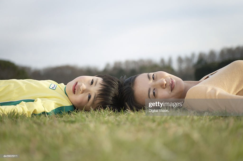 Surface Level Shot of a Mother and Son Lying Head to Head on Grass : Stock Photo