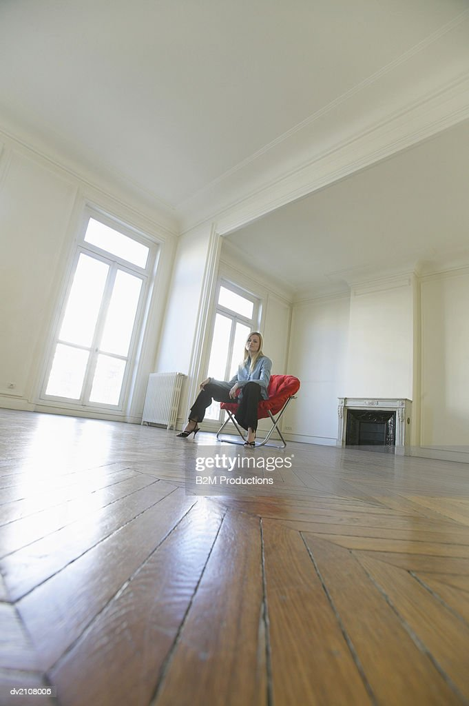 Surface Level Shot of a Woman Sitting on a Red Chair in a Large Empty Room with a Wooden Floor : Stock Photo