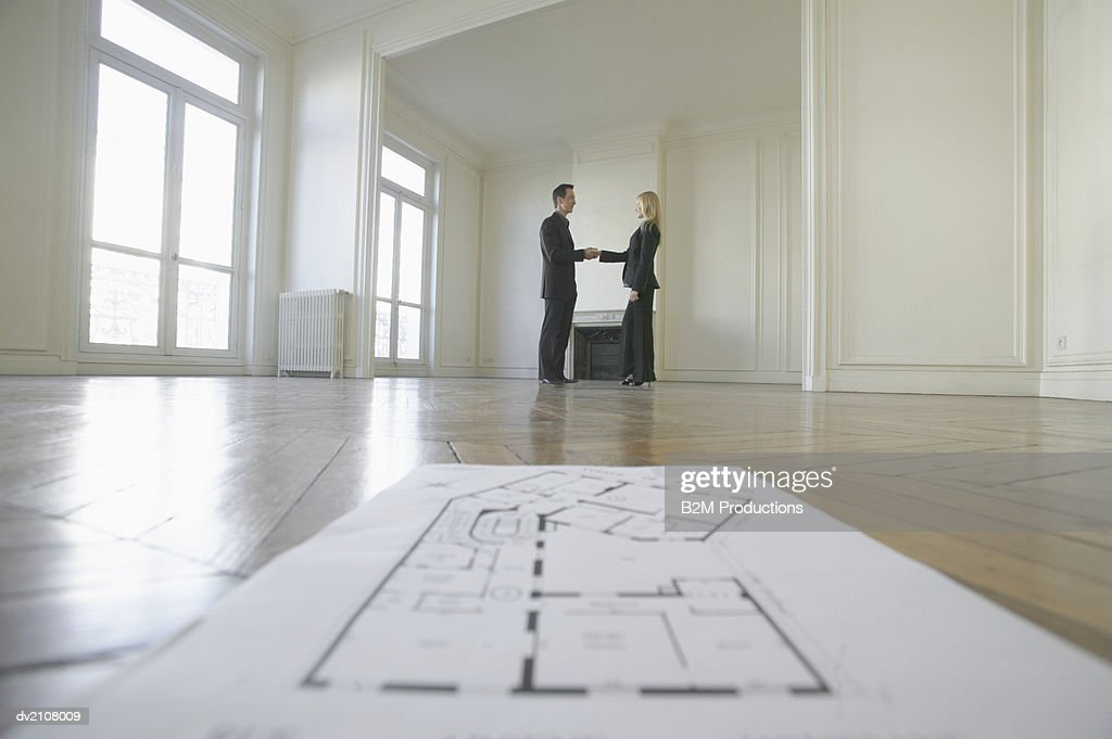 Surface Level Shot of Blueprints on a Wooden Floor in an Empty Room, with a Businessman Shaking Hands with a Businesswoman in the Background : Stock Photo