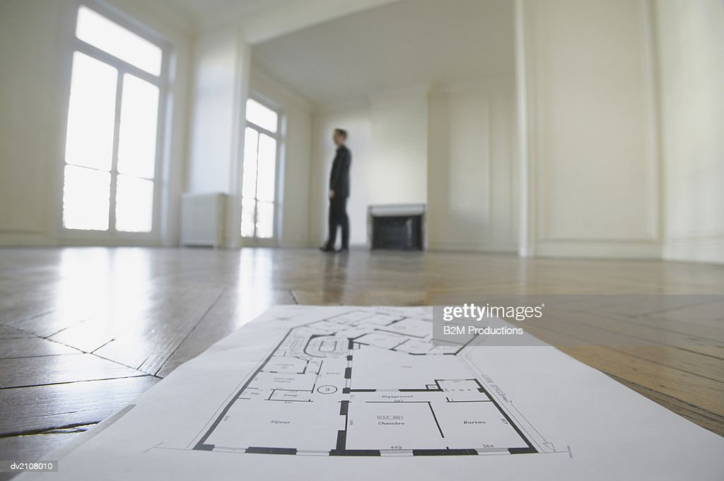Surface Level Shot of Blueprints on a Wooden Floor in an Empty Room, with a Businessman Standing in the Background : Stock Photo