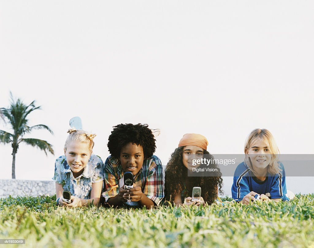 Surface Level Shot of Four Young Boys and Girls Lying on the Grass, Texting on Their Mobile Phones : Stock Photo