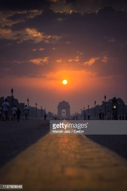 surface level shot of people on city street against sky during sunset - new delhi stock pictures, royalty-free photos & images