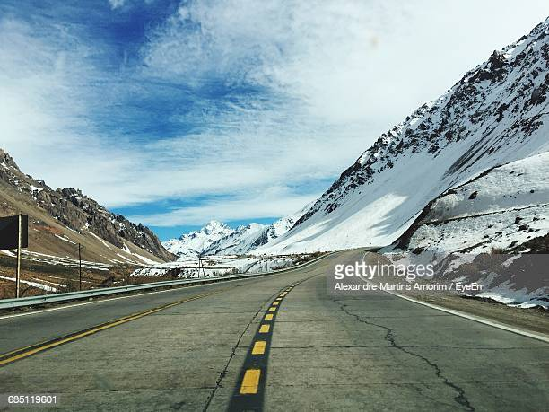 Surface Level Shot Of Road Amidst Snowcapped Mountains Against Sky