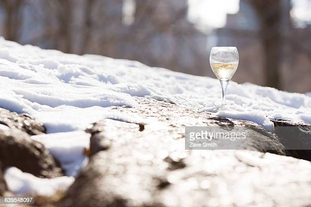 surface level view of a glass of white wine in snow - greedy smith stock pictures, royalty-free photos & images