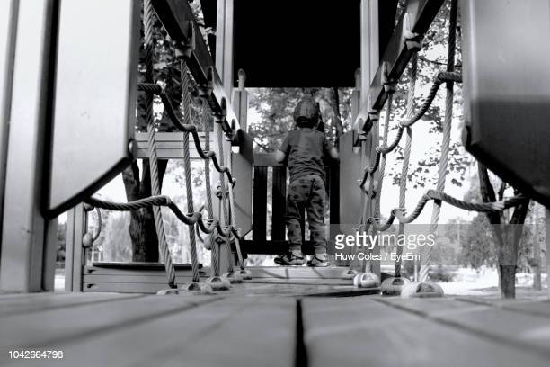 Surface Level View Of Boy Playing On Jungle Gym At Playground