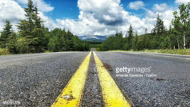 surface level view of country road against cumulus cloud - double yellow line stock photos and pictures