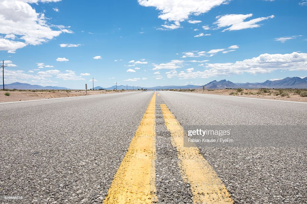 Surface Level View Of Country Road Against Sky In Desert : Stock-Foto