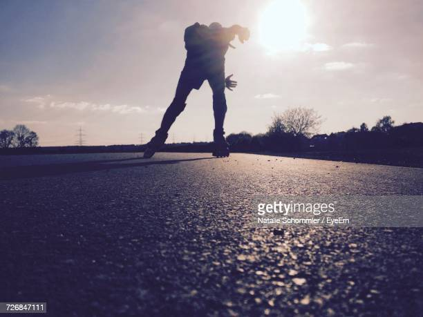 surface level view of man inline skating on road against sky - inline skate stock photos and pictures