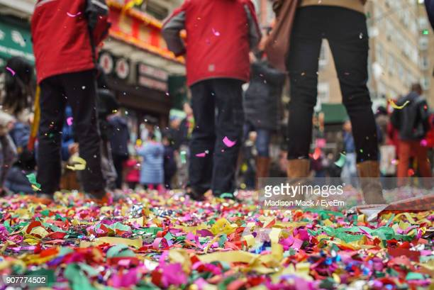 surface level view of people on colorful confetti in city - street fair stock photos and pictures