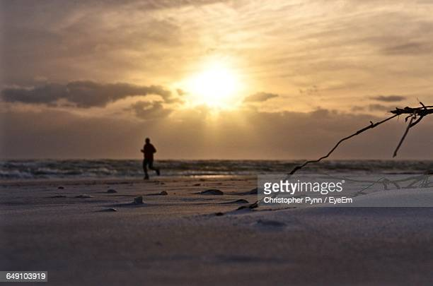 surface level view of sand with silhouette man running on shore at beach against sky during sunset - siesta key stock photos and pictures