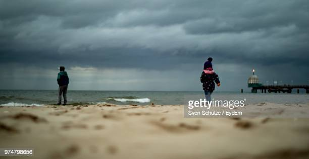 surface level view of siblings at beach against cloudy sky - 防寒着 ストックフォトと画像