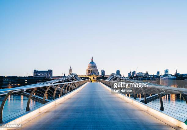 a surface level view of st.paul's cathedral and the millennium bridge at sunrise - stock photo - london stock pictures, royalty-free photos & images