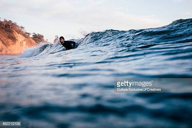 Surface level view of surfer lying on surfboard riding waves in ocean