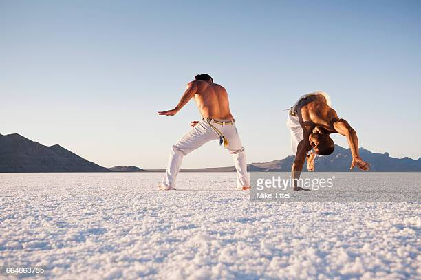 Surface level view of two men performing capoeira on Bonneville Salt Flats, Utah, USA
