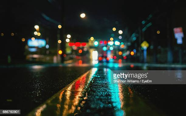 surface level view of wet street against illuminated city - double yellow line stock photos and pictures