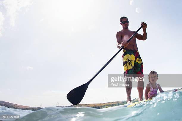 Surface level view of young man and toddler daughter standup paddleboarding