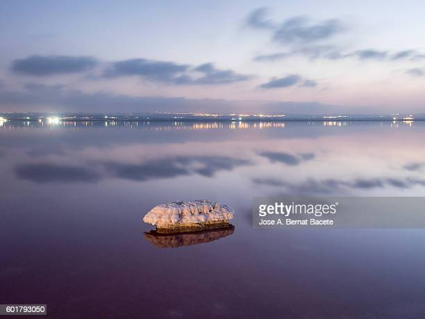 Surface of a great lake with his waters in calmness and with the reflections of the clouds and the lights of the city