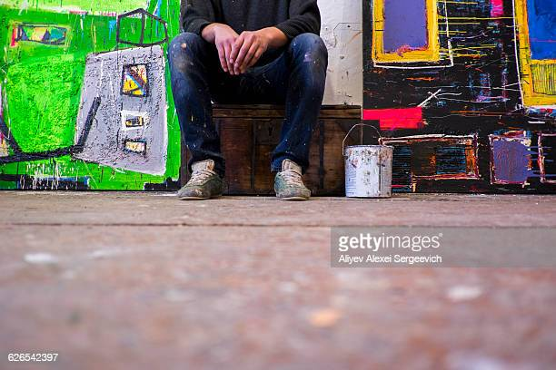 Surface view of male artist sitting between canvases